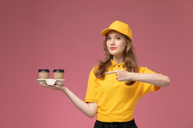 Junge kurierin der vorderansicht in der gelben uniform, die braune kaffeetassen des plastiks braun auf dem rosa schreibtischjobuniformlieferfarbdienstarbeiter hält