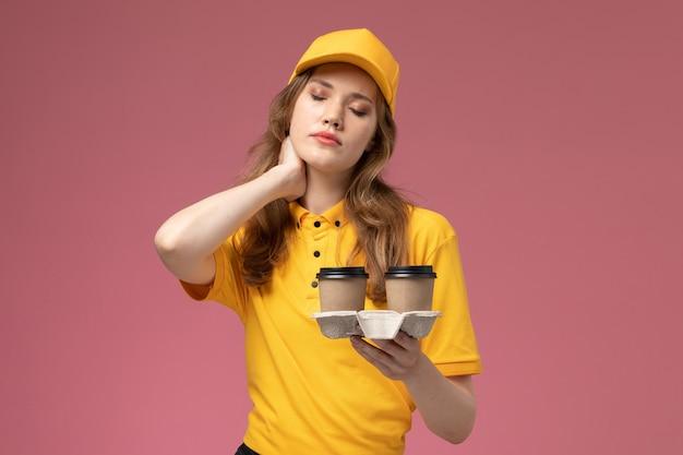 Junge kurierin der vorderansicht in der gelben uniform, die kaffeetassen hält, die kopfschmerzen auf rosa hintergrundschreibtischjobuniformlieferdienstarbeiter haben