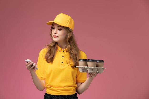 Junge kurierin der vorderansicht in der gelben uniform, die kaffeetassen hält und ihr telefon auf der weiblichen arbeiterin des dunkelrosa schreibtischuniformlieferdienstes verwendet