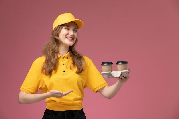 Junge kurierin der vorderansicht in der gelben uniform, die kaffeetassen mit lachen auf dem rosa hintergrundschreibtischjobuniformlieferdienstarbeiter hält