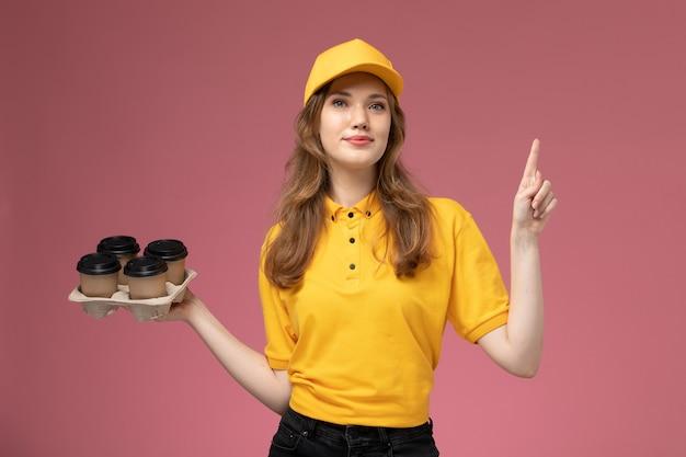 Junge kurierin der vorderansicht in der gelben uniform, die kaffeetassen mit leichtem lächeln auf dem rosa hintergrundschreibtischjobuniformlieferdienstarbeiter hält