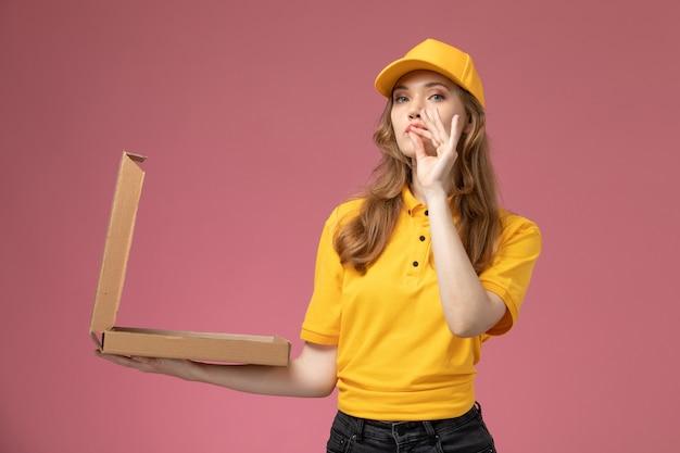 Junge kurierin der vorderansicht in der gelben uniform, die lebensmittelverpackung hält, die es auf weiblichem arbeiter des dunkelrosa schreibtischuniformlieferdienstes öffnet