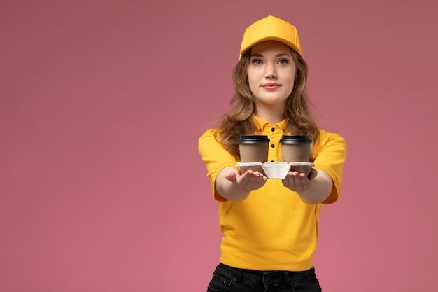 Junge kurierin der vorderansicht in der gelben uniform, die lieferkaffee mit lächeln auf dem rosa schreibtischjobuniformlieferdienstarbeiter hält