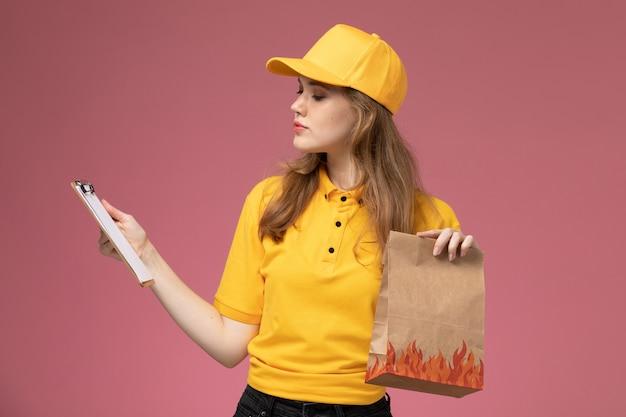 Junge kurierin der vorderansicht in der gelben uniform, die liefernahrungsmittelpaket zusammen mit notizblock auf rosa schreibtischjobuniformlieferdienstarbeiter hält