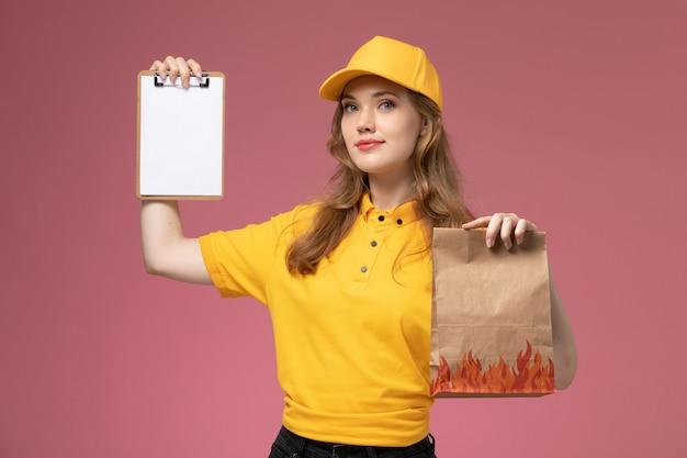 Junge kurierin der vorderansicht in der gelben uniform, die lieferung-nahrungsmittelpaket und kleinen notizblock auf rosa schreibtischjobuniform-zustelldienstarbeiter hält