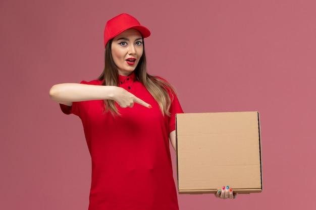 Junge kurierin der vorderansicht in der roten uniform, die leere nahrungsmittelbox auf rosa schreibtischdienstlieferuniformfirma hält