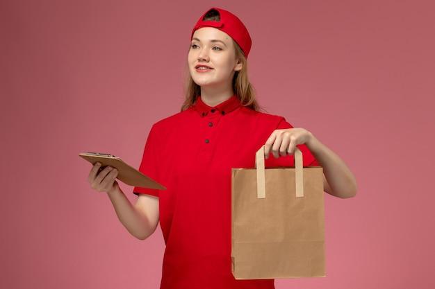 Junge kurierin der vorderansicht in der roten uniform, die lieferung-nahrungsmittelpaket und notizblock auf der hellrosa wand hält