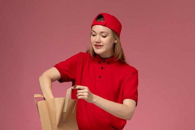 Junge kurierin der vorderansicht in der roten uniform und im umhang, die lieferung-nahrungsmittelpaket halten, das etwas von innen auf rosa wand nimmt