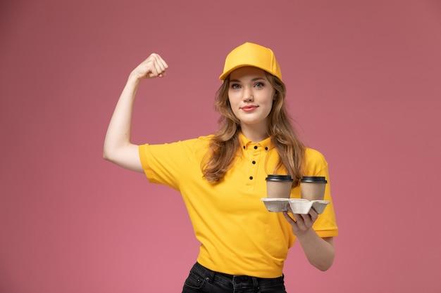Junge kurierin der vorderansicht in gelber uniform, die braune kaffeetassen aus kunststoff hält und sich auf dunkelrosa schreibtischjobuniform-lieferfarbdienstarbeiter beugt