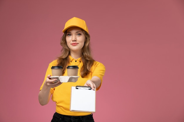 Junge kurierin der vorderansicht in gelber uniform, die plastikkaffeetassen und notizblock auf dem dunkelrosa schreibtischuniform-lieferservicearbeiter hält
