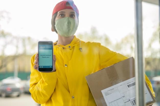 Junge kurierin in arbeitskleidung und maske, die transaktionsdaten auf dem smartphonebildschirm zeigt