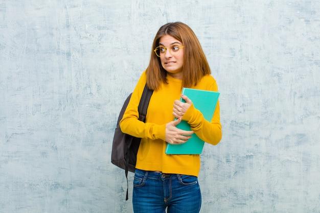 Junge kursteilnehmerfrau, die gesorgt, betont, besorgt und erschrocken schaut, zähne in panik versetzt und zusammengebissen