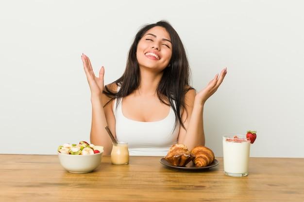 Junge kurvige frau, die ein frohes frühstück viel lachen nimmt