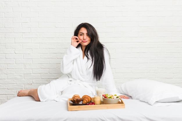 Junge kurvige frau, die ein frühstück auf dem bett mit den fingern auf den lippen nimmt, die ein geheimnis halten.