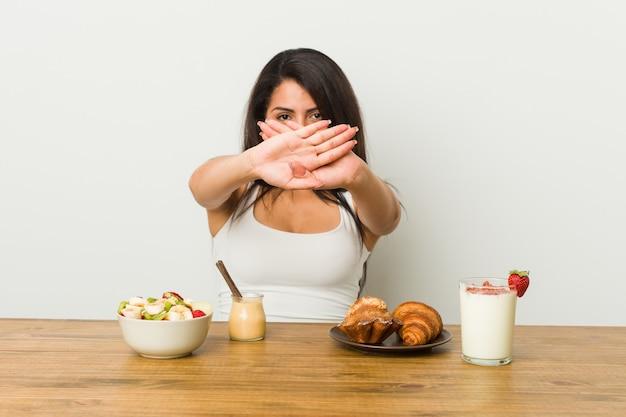 Junge kurvige frau, die ein frühstück macht, das eine verweigerungsgeste tut