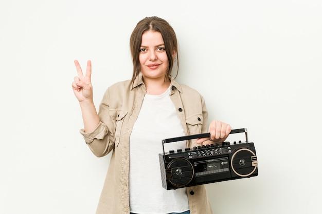 Junge kurvige frau, die ein retro-radio hält, das nummer zwei mit den fingern zeigt.