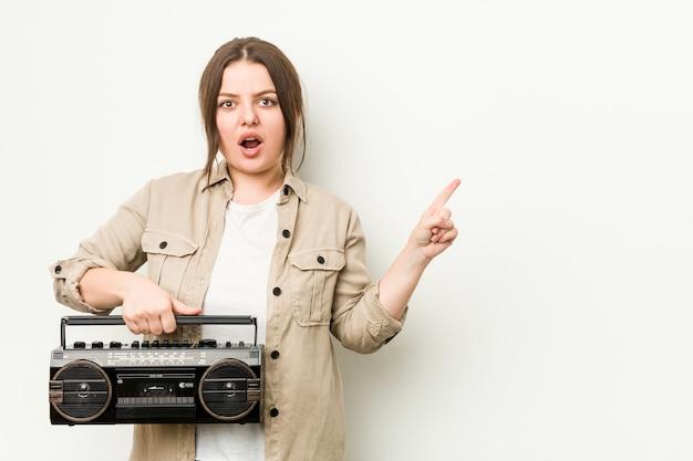 Junge kurvige frau, die ein retro-radio hält, das zur seite zeigt