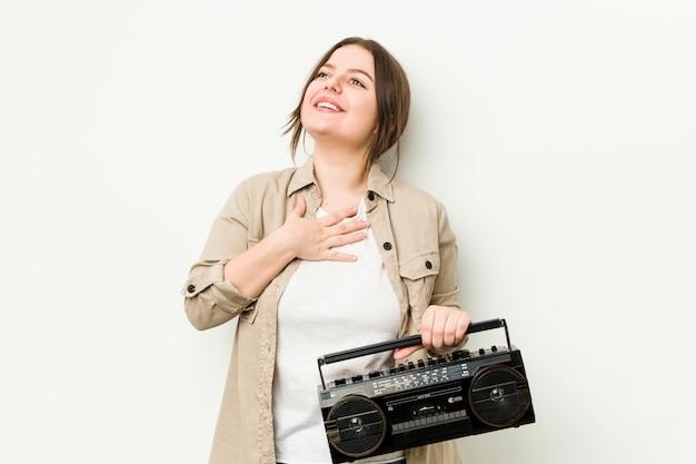 Junge kurvige frau, die ein retro-radio hält, lacht laut und hält hand auf brust.