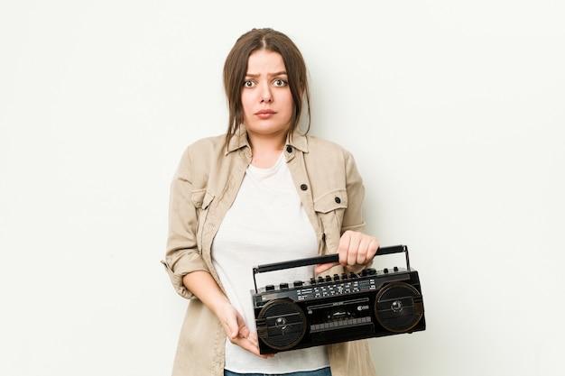 Junge kurvige frau, die ein retro-radio hält, zuckt mit den schultern und offenen augen verwirrt.