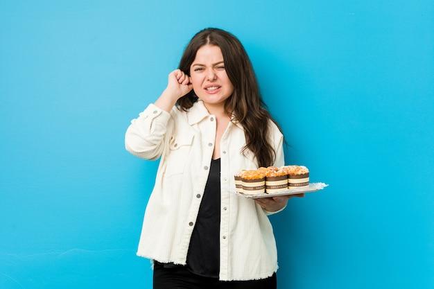 Junge kurvige frau, die einen cupcakes hält, der ohren mit händen bedeckt.