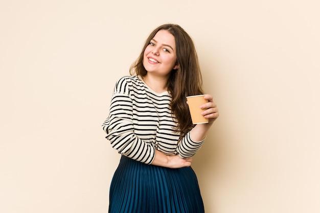 Junge kurvige frau, die einen kaffee hält, der lacht und spaß hat.