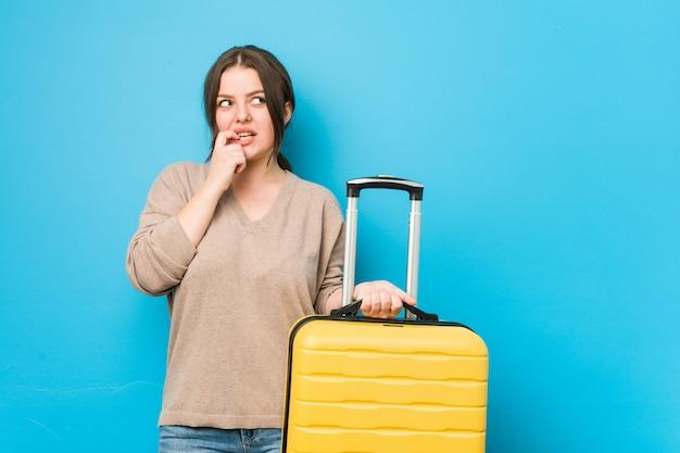 Junge kurvige frau, die einen koffer hält, entspannte sich und dachte an etwas, das einen kopienraum betrachtete.