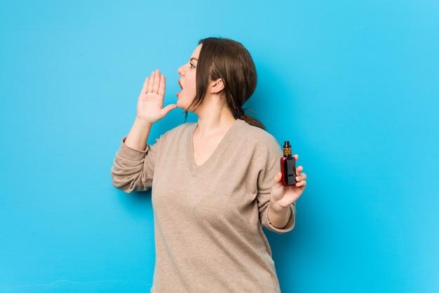 Junge kurvige frau, die einen vaporizer hält, der schreit und handfläche nahe geöffnetem mund hält.