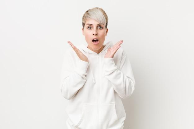 Junge kurvige frau, die einen weißen kapuzenpulli trägt, überrascht und schockiert.