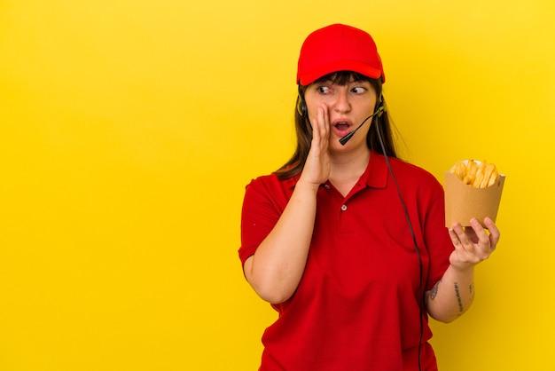 Junge kurvige kaukasische fast-food-restaurantarbeiterin, die pommes auf blauem hintergrund hält, sagt eine geheime heiße bremsnachricht und schaut beiseite