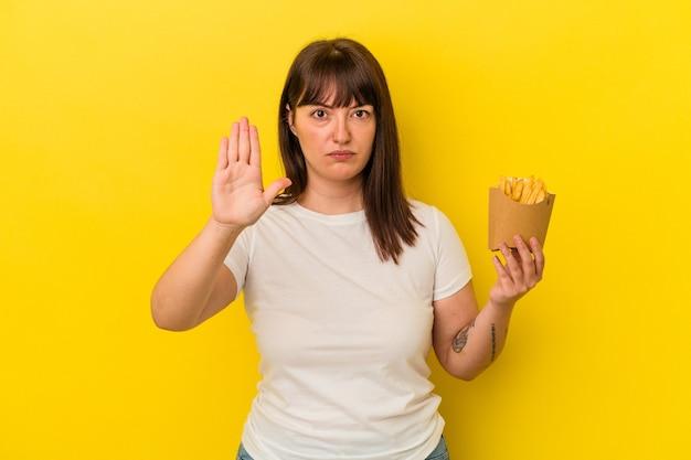 Junge kurvige kaukasische frau, die pommes auf gelbem hintergrund hält, die mit ausgestreckter hand steht und stoppschild zeigt und sie verhindert.
