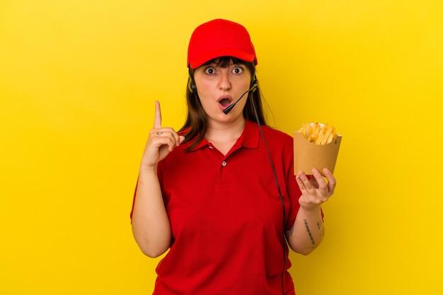 Junge kurvige kaukasische frau fast-food-restaurant-arbeiter mit pommes auf blauem hintergrund isoliert mit einer großartigen idee, konzept der kreativität.