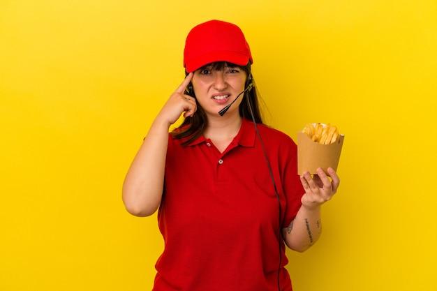 Junge kurvige kaukasische frau fast-food-restaurantangestellter, die pommes auf blauem hintergrund isoliert hält und eine enttäuschungsgeste mit dem zeigefinger zeigt.