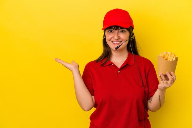 Junge kurvige kaukasische frau fast-food-restaurantarbeiterin, die pommes auf blauem hintergrund isoliert hält, die einen kopienraum auf einer handfläche zeigt und eine andere hand an der taille hält.