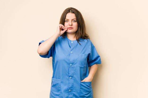 Junge kurvige krankenschwesterfrau mit den fingern auf den lippen, die ein geheimnis halten.