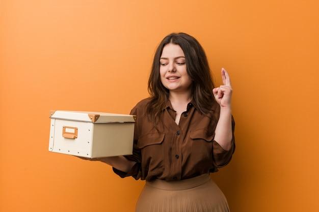 Junge kurvige plusgrößenfrau, die eine box hält, die finger für glück kreuzt