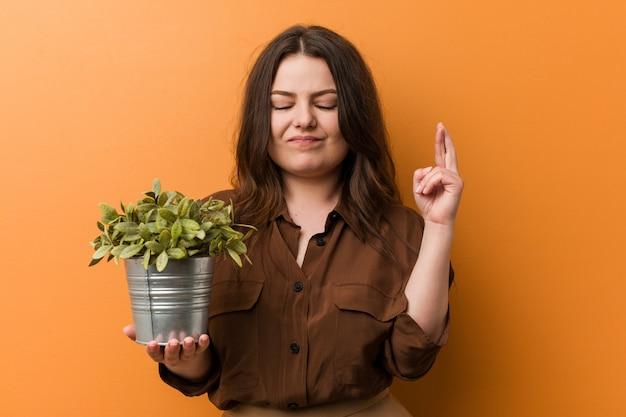 Junge kurvige plusgrößenfrau, die eine pflanze hält, die finger für glück kreuzt