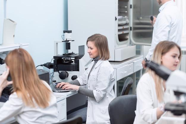 Junge laborassistenten, die laptop für chemisches laborexperiment verwenden