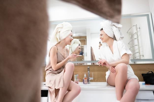 Junge lachende europäische frauen sitzen auf dem waschbecken im badezimmer. freundinnen mit augenklappen im gesicht und eingewickelten badetüchern auf dem kopf. konzept der gesichtspflege. innenraum der modernen wohnung