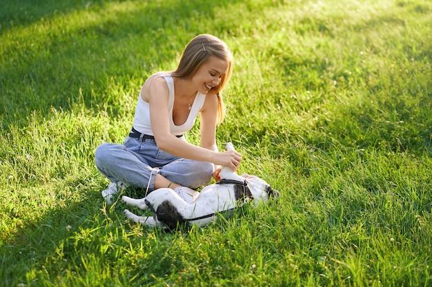 Junge lachende frau, die auf gras in lotushaltung mit französischer bulldogge sitzt und spaß hat. wunderschönes kaukasisches kaukasisches mädchen, das warmen sommertag mit hund genießt, reinrassigen hund im stadtpark streichelnd.
