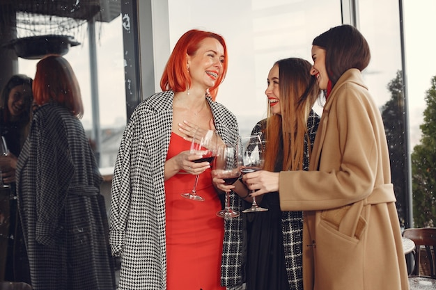Junge lachende freunde, die draußen roséwein aus glas trinken