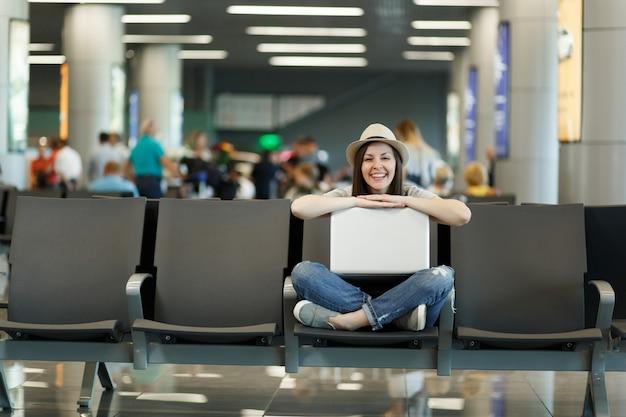 Junge lachende reisende touristenfrau, die mit laptop mit gekreuzten beinen sitzt, während sie in der lobbyhalle am internationalen flughafen wartet?