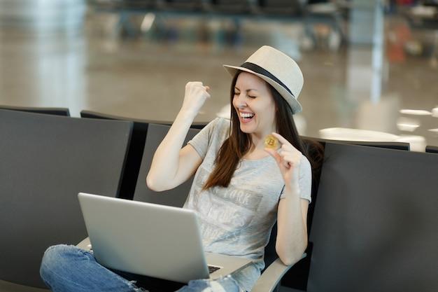 Junge lachende reisende touristenfrau mit hut sitzt am laptop und hält bitcoin und macht gewinnergeste, die in der lobbyhalle am flughafen wartet?