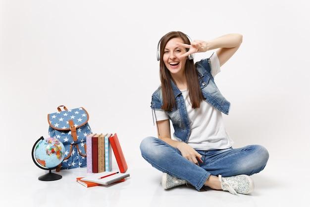 Junge lachende studentin mit kopfhörern, die musik hören, die ein victory-zeichen zeigt, das in der nähe des globus sitzt, rucksack, schulbücher isoliert