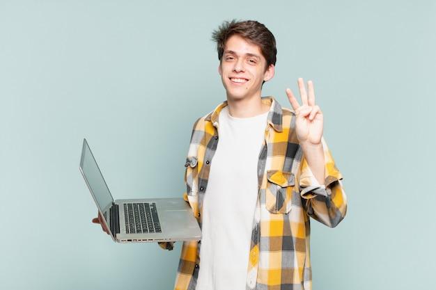 Junge lächelnd und freundlich aussehend, nummer drei oder dritte mit der hand nach vorne zeigend, herunterzählen. laptop-konzept