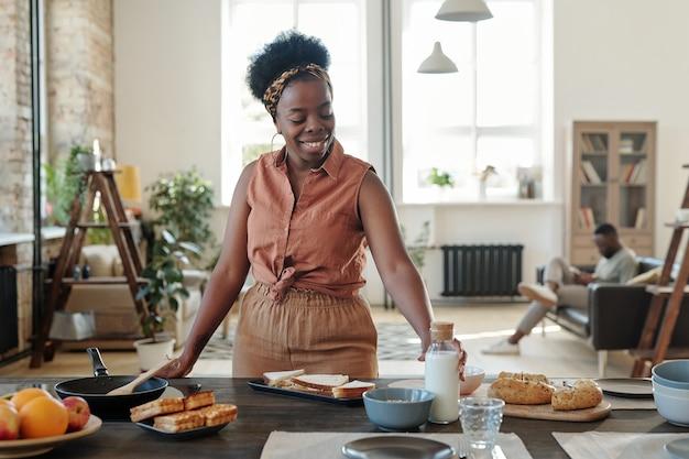 Junge lächelnde afrikanerin in freizeitkleidung, die am elektroherd steht und eine flasche milch nimmt, während sie das abendessen für ihre familie in der küche kocht