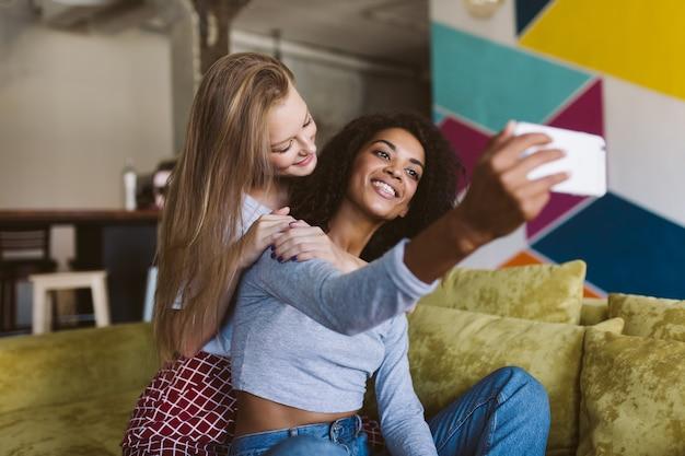 Junge lächelnde afroamerikanerfrau mit dunklem haar und hübsche frau mit blondem haar, die glücklich fotos auf handy macht, während zeit zusammen zu hause verbringend