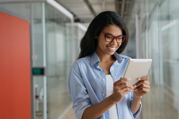 Junge lächelnde afroamerikanerin, die digitales tablett verwendet, das videos online ansieht