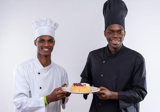 Junge lächelnde afroamerikanische köche in der kochuniform halten kuchen auf teller zusammen lokalisiert auf weißer wand