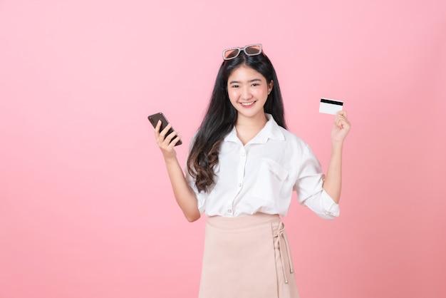Junge lächelnde asiatische frau, die kreditkarte mit smartphone hält