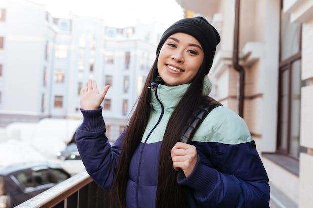Junge lächelnde asiatische frau in der warmen kleidung